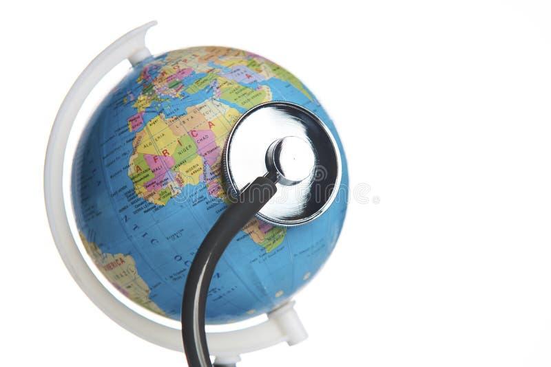 Stéthoscope médical enroulé autour du globe image stock