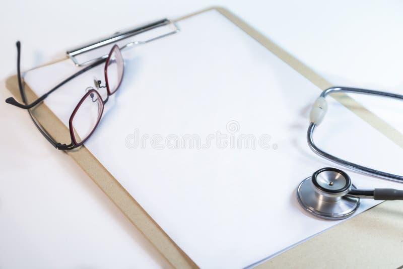 Stéthoscope médical sur le presse-papiers et les verres blancs de docteur sur la table blanche photo stock