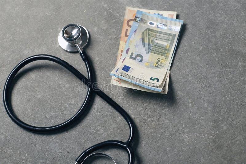 Stéthoscope noir et euro argent au-dessus de fond gris, de soins de santé et de concept financier médical photographie stock