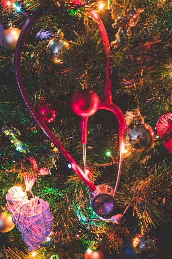 Stéthoscope rouge accrochant sur un arbre de Noël décoré Noël médical photo stock