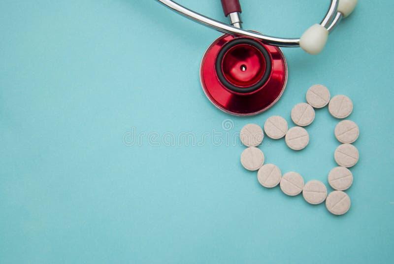 Stéthoscope rouge avec les comprimés, pilules sur le fond bleu Copiez l'espace Médecine, concept de heartbeast images libres de droits
