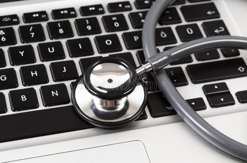 Stéthoscope se tenant sur le clavier d'ordinateur d'isolement sur le blanc images libres de droits