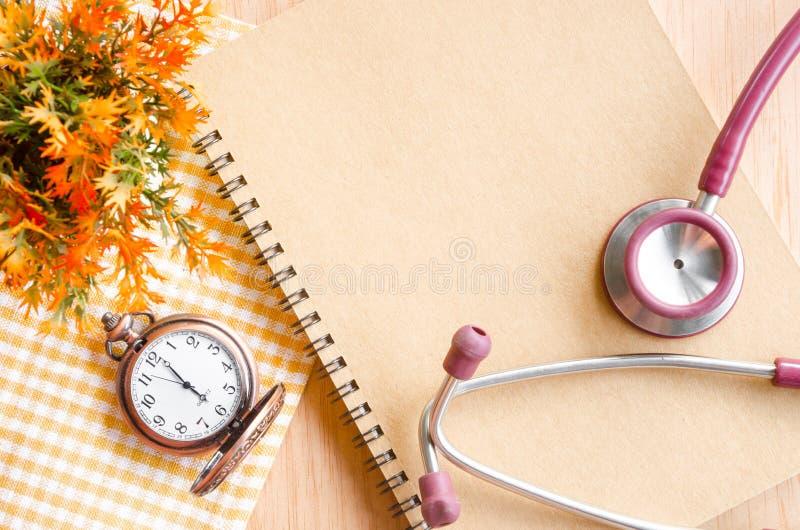 Stéthoscope sur le journal intime et l'horloge de vintage photos stock