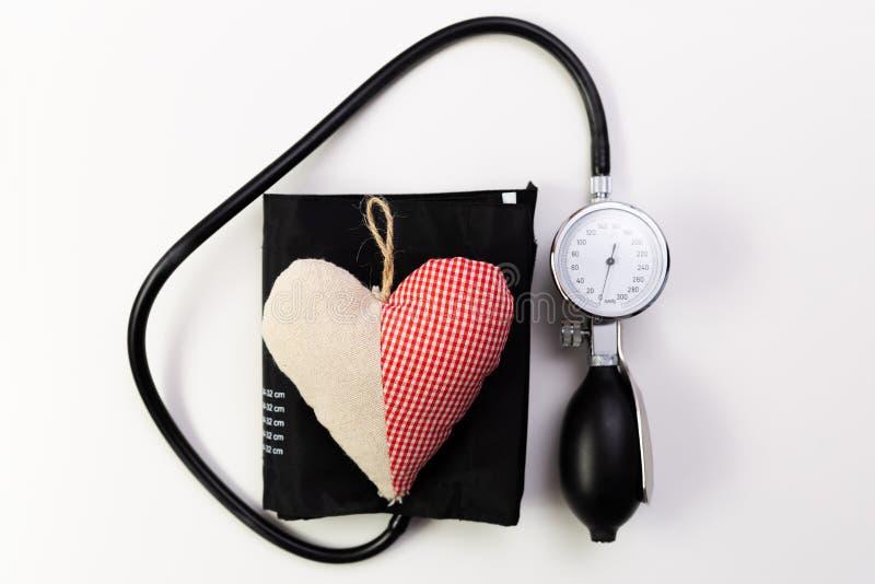 Stéthoscope sur un petit morceau blanc de fond un coeur de coton sur le dessus Il photos stock