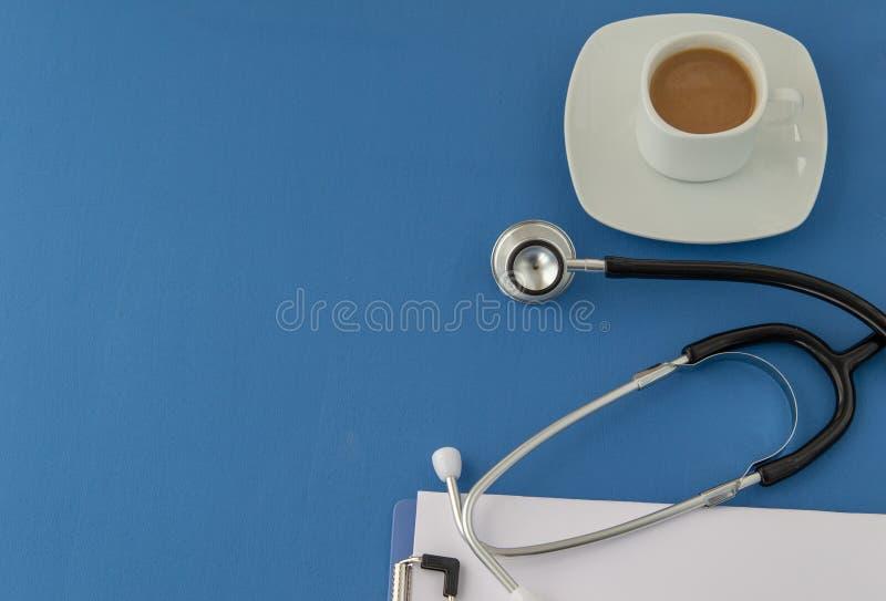 Stéthoscope, tasse de café sur un fond bleu st?thoscope r?gl? d'argent de m?decine de mensonges de concept images stock