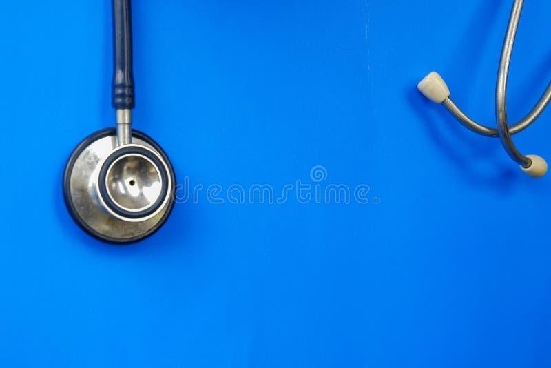 Stéthoscope utilisé accrochant au-dessus du fond bleu images stock
