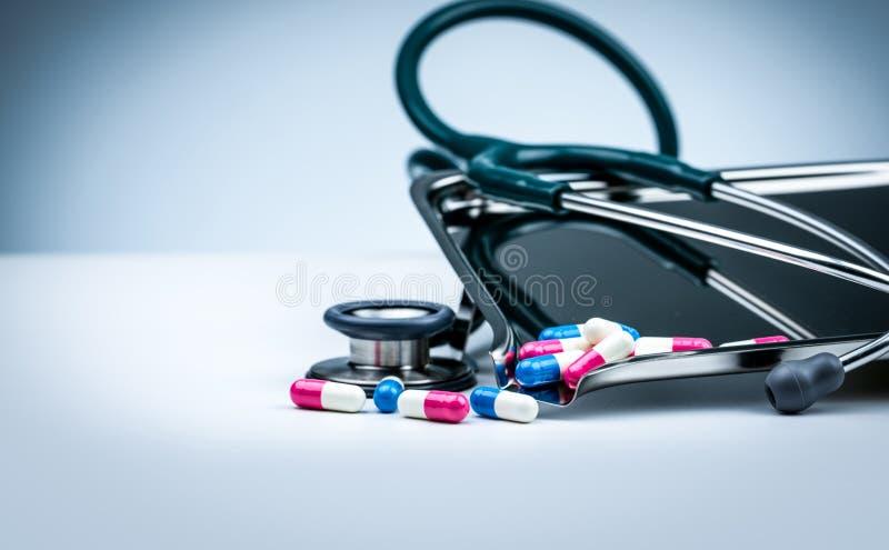 Stéthoscope vert avec la pile des pilules antibiotiques de capsule sur le plateau de drogue et de la diffusion sur la table blanc images stock