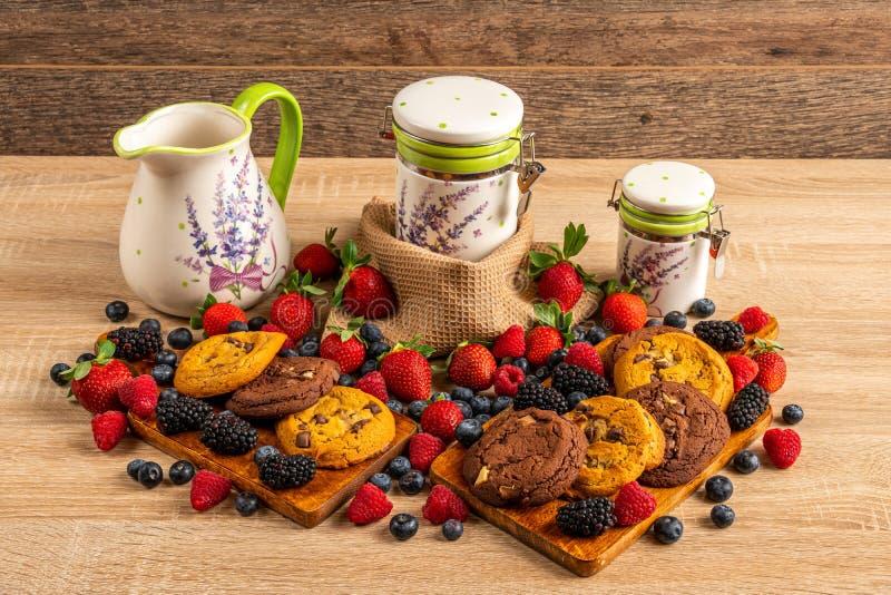 Stół brogujący z malinkami, czarnymi jagodami, ciastkami i ceramicznymi odbiorcami, obrazy stock
