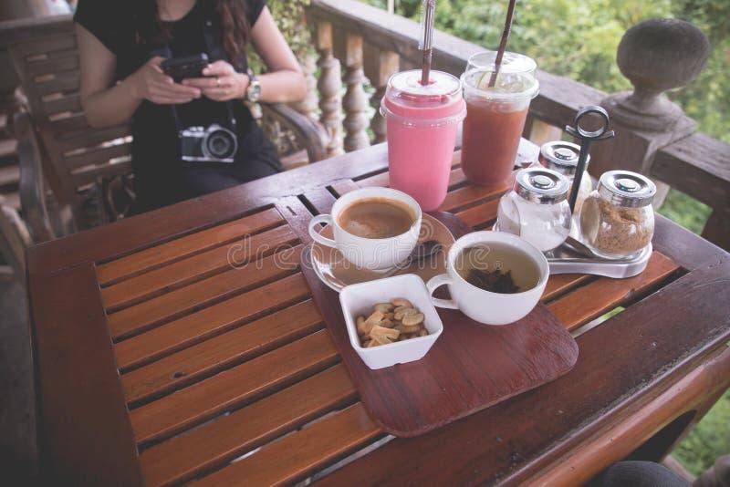 Stół drewniany z czarną filiżanką kawy i zimnym truskawkowym wygładzeniem obraz royalty free