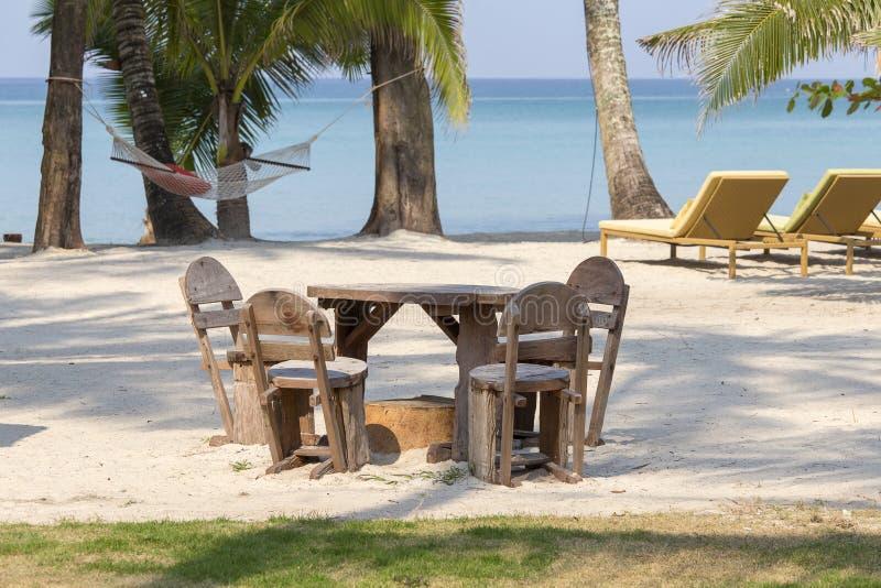Stół i drewniani krzesła w pustej kawiarni obok wody morskiej na tropikalnej plaży, Tajlandia z bliska zdjęcia stock