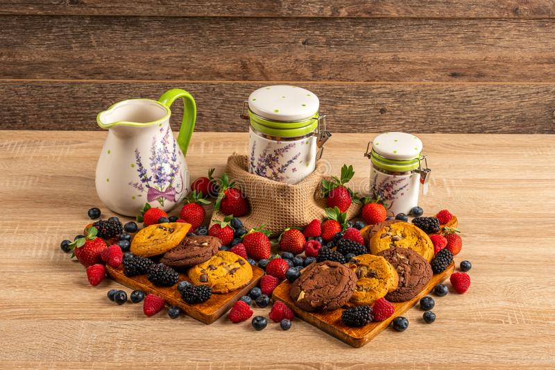 Stół pełno malinki, lasowe owoc i czekoladowi ciastka, zdjęcie royalty free