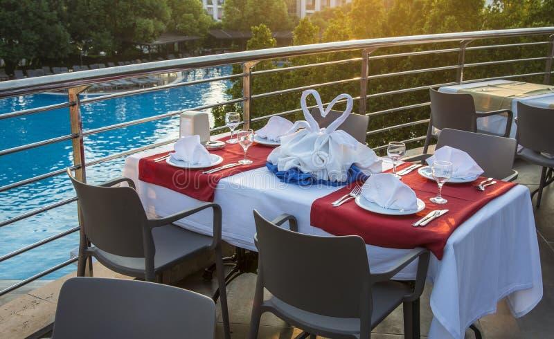 Stół z krzesłami słuzyć dla pary na basenu tle Romantyczny wydarzenie plenerowy Wakacje pojęcie zdjęcie stock