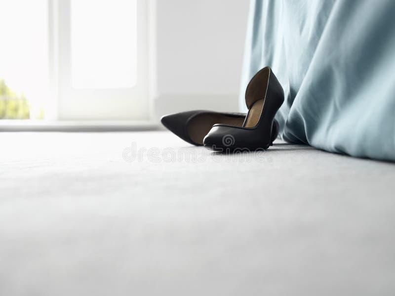 Stöckelschuhe durch Bett stockfoto