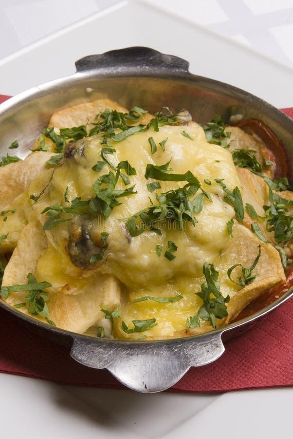 Stör gebraten unter Kartoffeln und Käse stockbilder