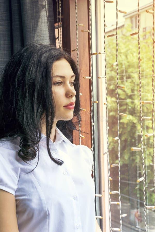 Störande flicka som poserar det inre near fönstret arkivfoto