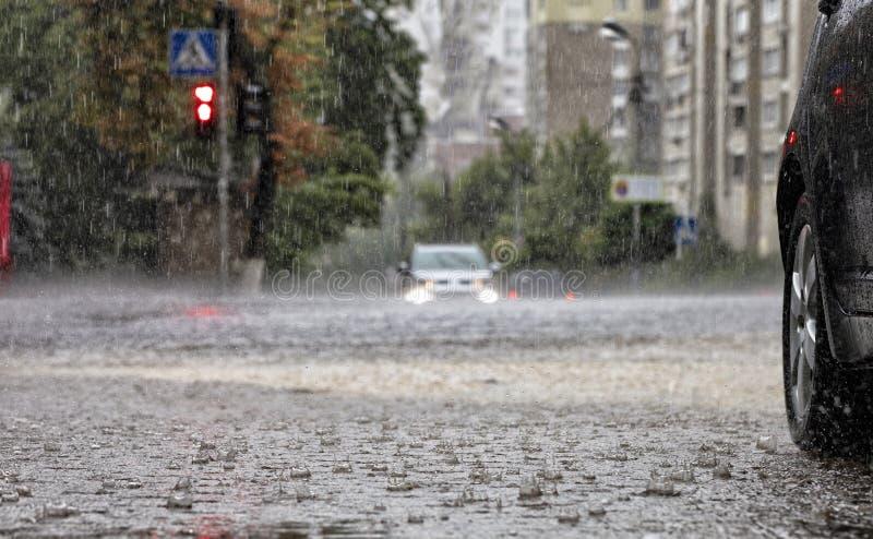 Störtregn på vägen och på trottoaren som bevattnar bilar som står på tvärgatorna royaltyfria bilder