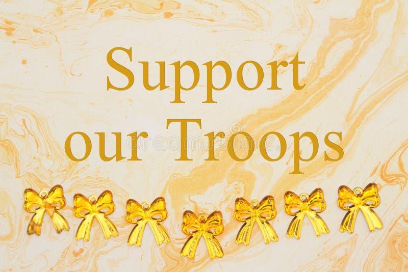 Stötta vårt soldatmeddelande med gula band på texturerat vattenfärgpapper arkivbilder