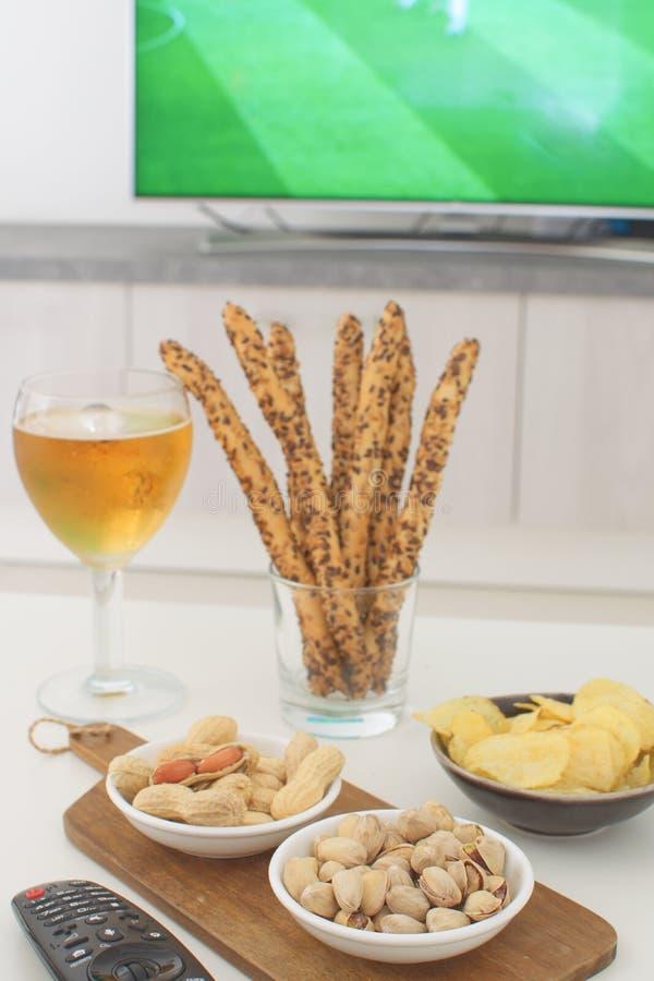 Stöttande öl för mat för landslagbegreppsfotbollsfan, jordnötter, pistacios, potatischiper och tvfjärrkontroll royaltyfria bilder