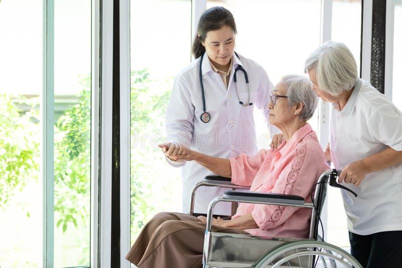 Stöttande handikappade personer för doktor eller för sjuksköterska, alzheimer hög asiatisk kvinna på rullstolen, kvinnlig anhörig royaltyfria bilder