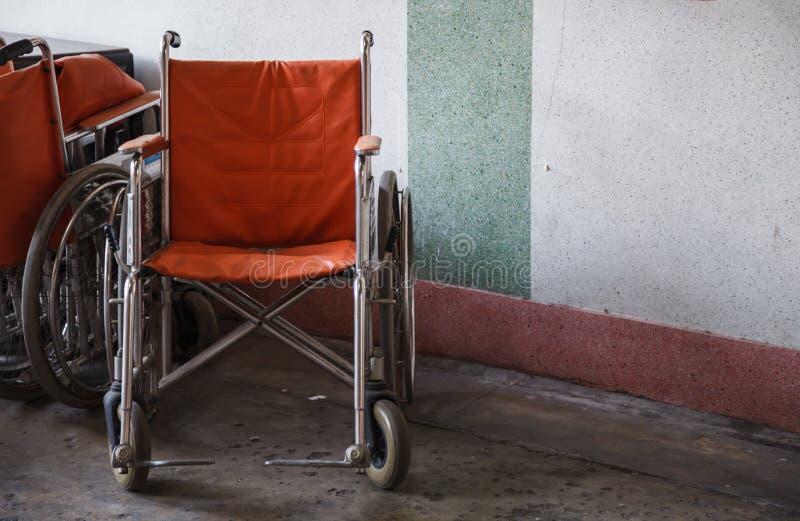 Stöttande rullstolar för åldring, pensionären som var rörelsehindrad i hörnbakgrund, använde, när det är svårt att gå eller omöjl arkivbild