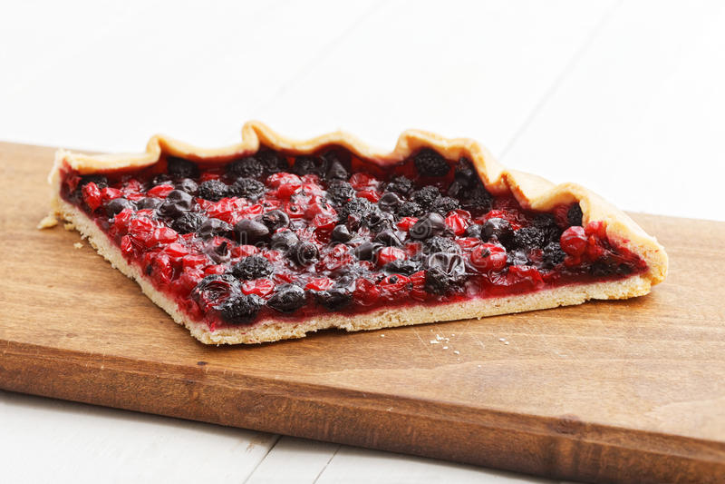 Stück der selbst gemachten Torte mit Beeren auf Küchenschneidebrett lizenzfreie stockfotografie