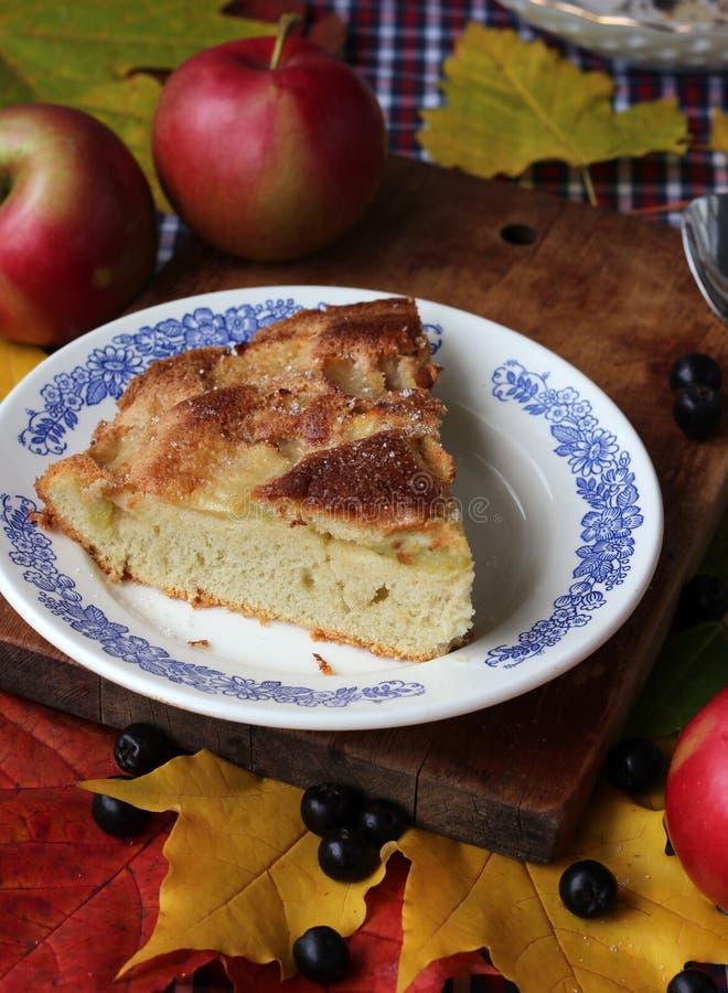 Stück der Torte, des Herbstlaubs und der roten Äpfel auf dem Tisch mit stockbild