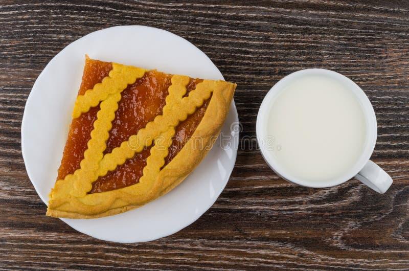Stück der Torte mit Aprikosenmarmelade in der Platte und in der Milch stockbild