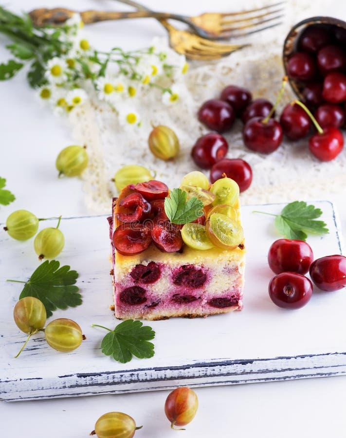 Stück der Torte von den Beeren der Kirsche und des Hüttenkäses stockfoto