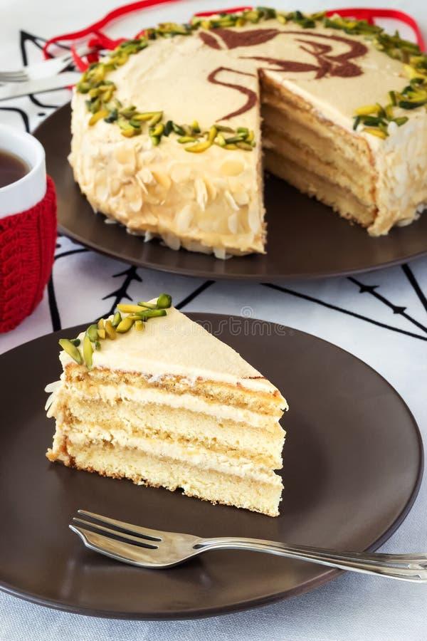 Stück des überlagerten Kuchens der Mokka mit Buttercreme, Pistazie, Becher im roten Strickhemd, Nahaufnahmeweißhintergrund lizenzfreies stockfoto