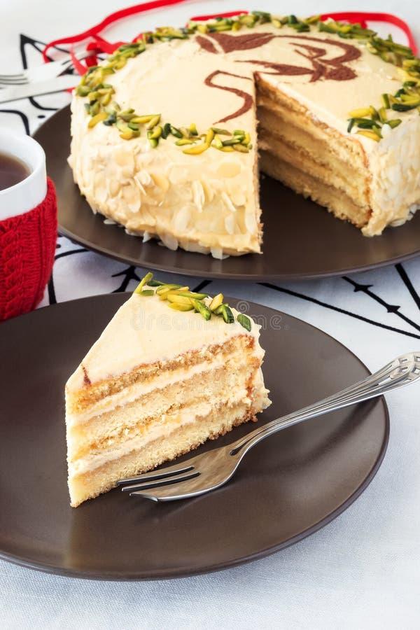 Stück des überlagerten Kuchens der Mokka mit Buttercreme, Pistazie, Becher im roten Strickhemd, Nahaufnahmeweißhintergrund lizenzfreies stockbild