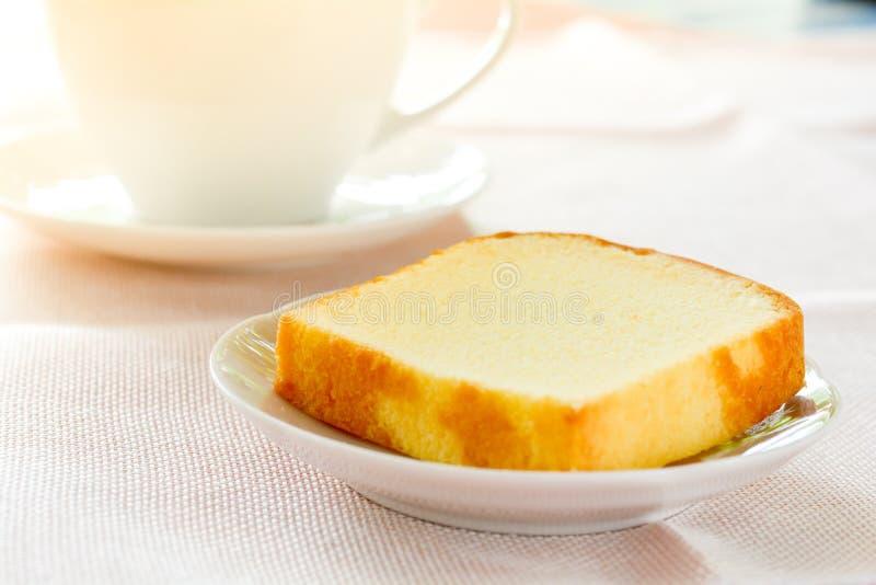 Stück des Butterkuchens auf dem weißen Teller gedient mit Schale schwarzem Kaffee Zeiten, sich Konzept zu entspannen stockfotografie