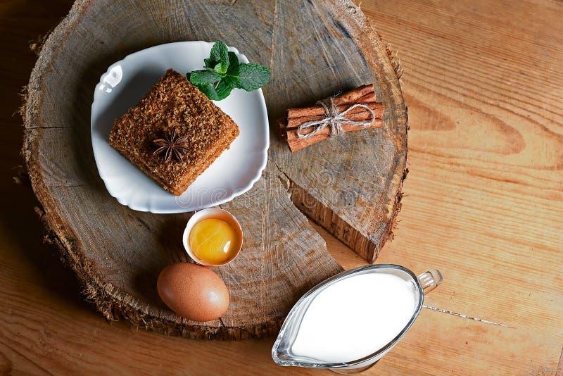 Stück des gegossenen Honigkuchens mit Sahne auf Platte, verziert mit Anis und einem Bündel Minze, Eiern, Milch, Zimtstangen und K stockfotografie