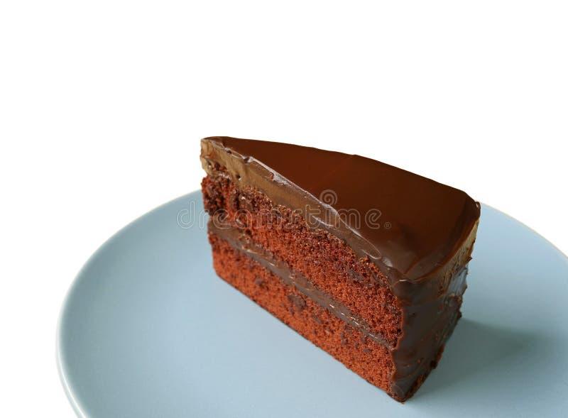 Stück des köstlichen Schokoladen-Schicht-Teegebäcks gedient auf der blauen Platte lokalisiert auf weißem Hintergrund lizenzfreie stockfotografie