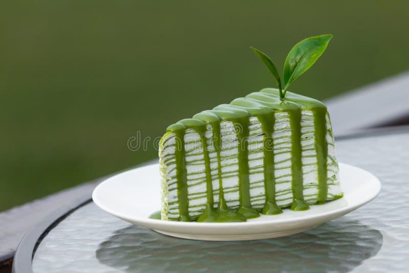 Stück des Kuchens des grünen Tees auf Glastisch stockfotos