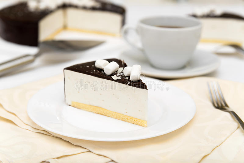 Stück des Kuchens mit Auflauf ` Vogel ` s Milch `, Keks, Kremeis und dunkler Schokolade auf einer weißen Platte lizenzfreie stockfotos