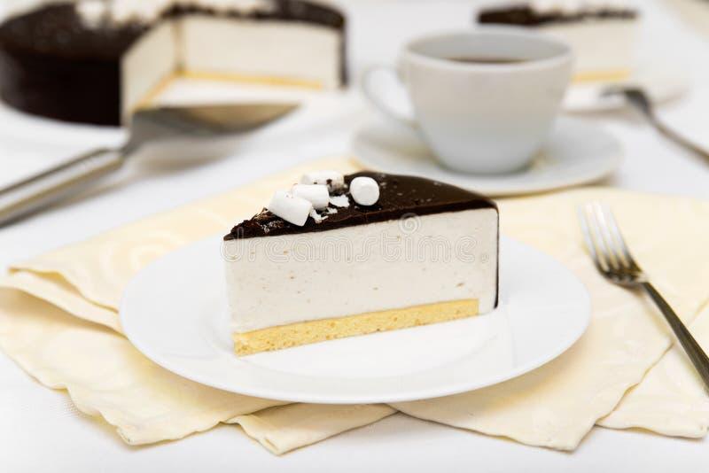 Stück des Kuchens mit Auflauf ` Vogel ` s Milch `, Keks, Kremeis und dunkler Schokolade auf einer weißen Platte lizenzfreies stockfoto