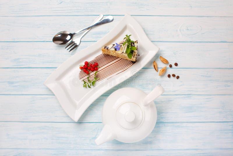 Stück des Kuchens, Tee in einer Teekanne auf blauen Brettern stockbilder