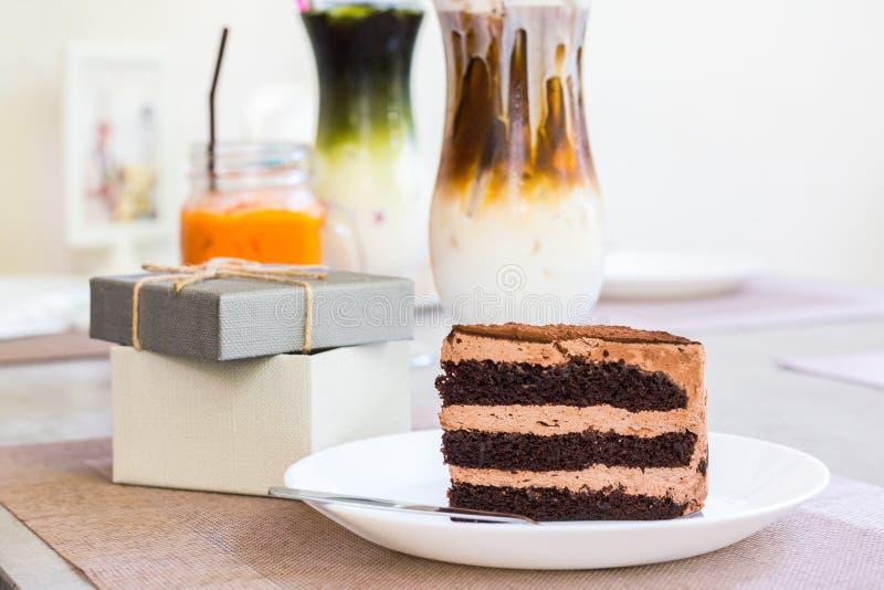 Stück des Schokoladenkuchens und -gabel im Teller auf dem Tisch nahe Geschenkbox auf dem Tisch lizenzfreies stockfoto