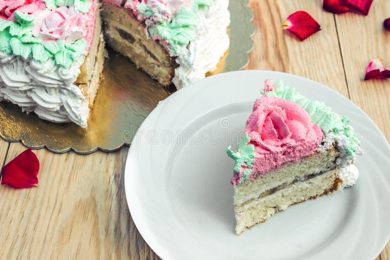 Stück des Schwammkuchens mit Klumpencreme und -banane auf Hintergrund des Kuchens stockbild