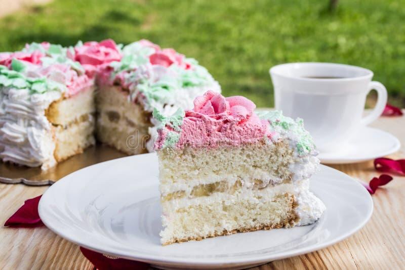 Stück des Schwammkuchens mit Klumpencreme und -banane auf Hintergrund des Kuchens und des Tasse Kaffees lizenzfreie stockbilder