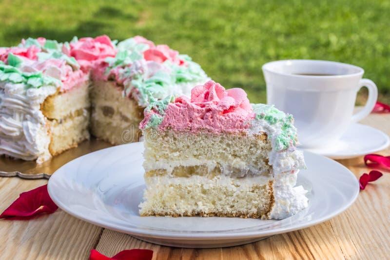 Stück des Schwammkuchens mit Klumpencreme und -banane auf Hintergrund des Kuchens und des Tasse Kaffees stockfoto