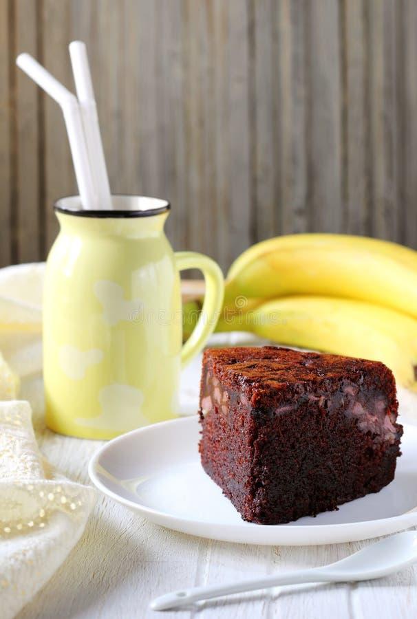 Stück des selbst gemachten Schokoladenkuchens mit Bananen auf einer weißen Platte stockfotografie