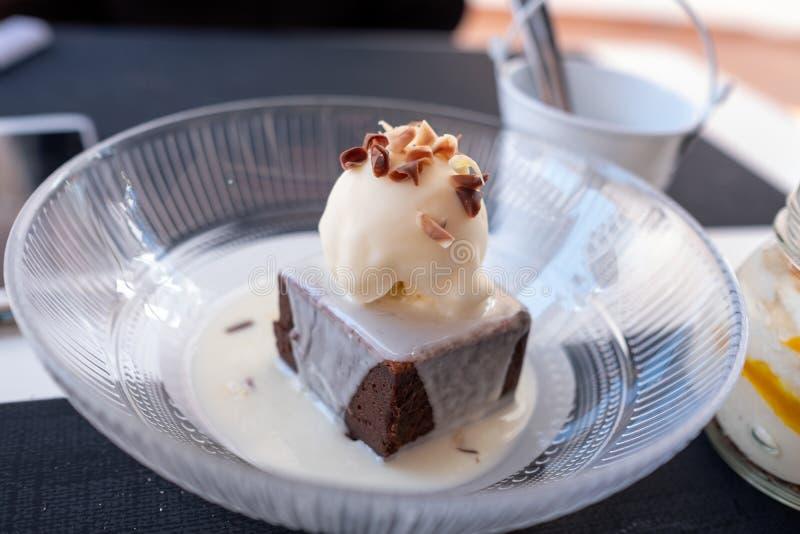 Stück dunkle Schokolade mit einem Ball des Vanilleeises verziert mit Nüssen auf weißem Schokoladenhintergrund lizenzfreie stockfotografie