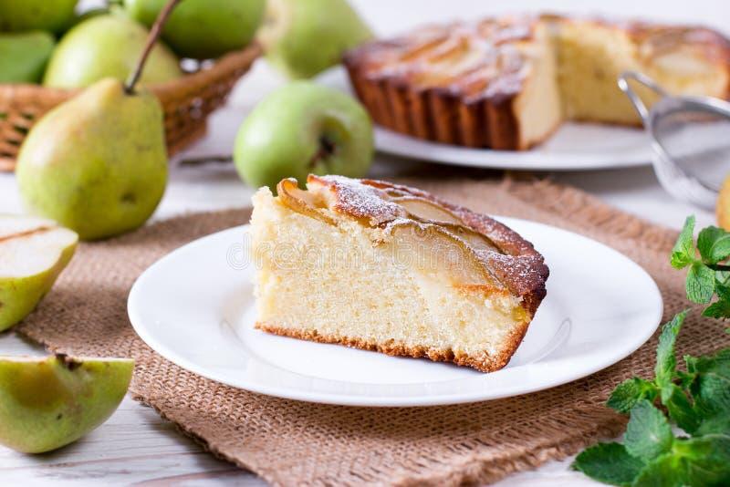 Stück eines Birnenkuchens auf einer weißen Platte auf einer weißen Tabelle stockbild