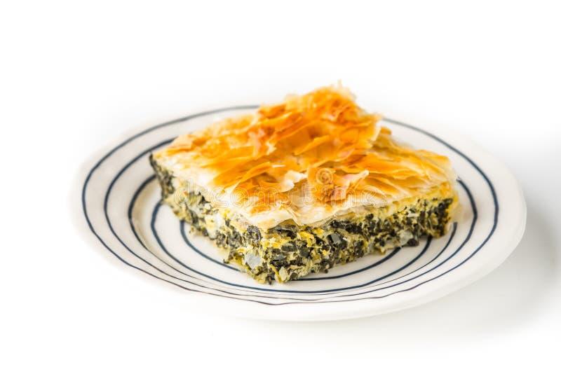 Stück griechisches Torte spanakopita auf der keramischen Platte auf dem weißen Hintergrund stockbild