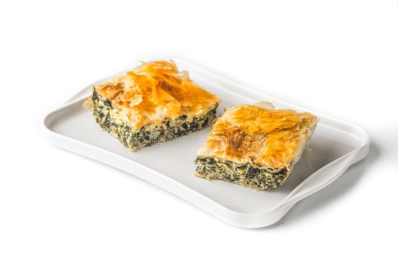 Stück griechisches Torte spanakopita auf der weißen Platte auf dem weißen Hintergrund lizenzfreie stockfotos