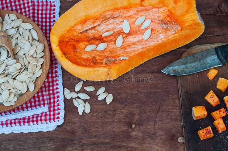 Stück Kürbis und Kürbiskerne auf einem braunen Holztisch stockbild