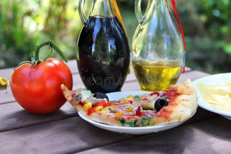 Stück Pizza im Sommergartentisch lizenzfreie stockbilder