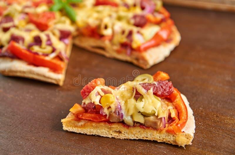 Stück Pizza lokalisiert mit Salami, Tomaten, grünem Pfeffer, Zwiebel, grünen Oliven, Mais, Käse und Gewürzen auf braunem Holztisc stockfoto