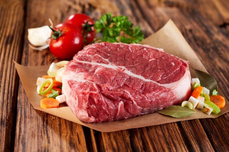 Stück rohes Fleisch verziert mit Gemüse lizenzfreie stockfotos